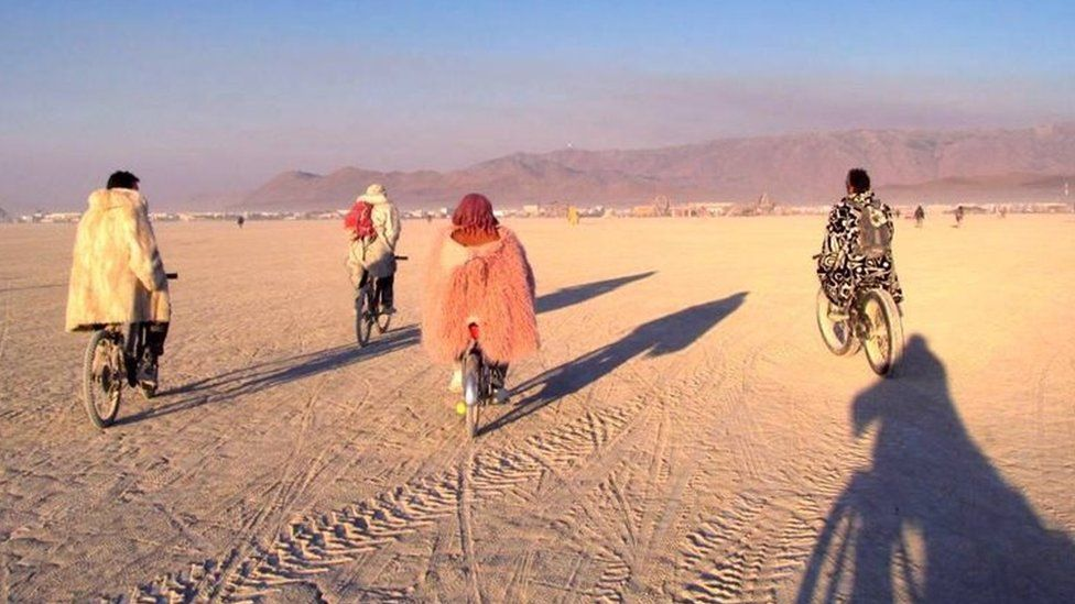 Four people riding bikes at Burning Man