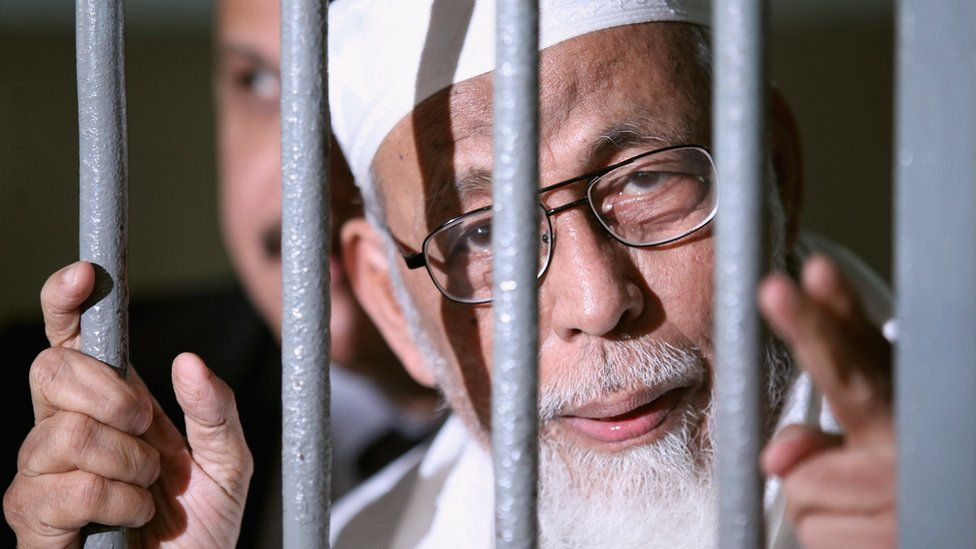 Muslim cleric Abu Bakar Ba'asyir is seen behind bars before his hearing verdict at the South Jakarta District Court on June 16, 2011