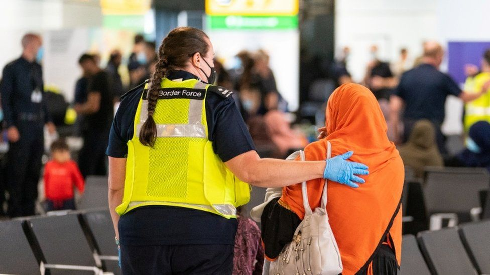An Afghan woman is shown to seating in Heathrow