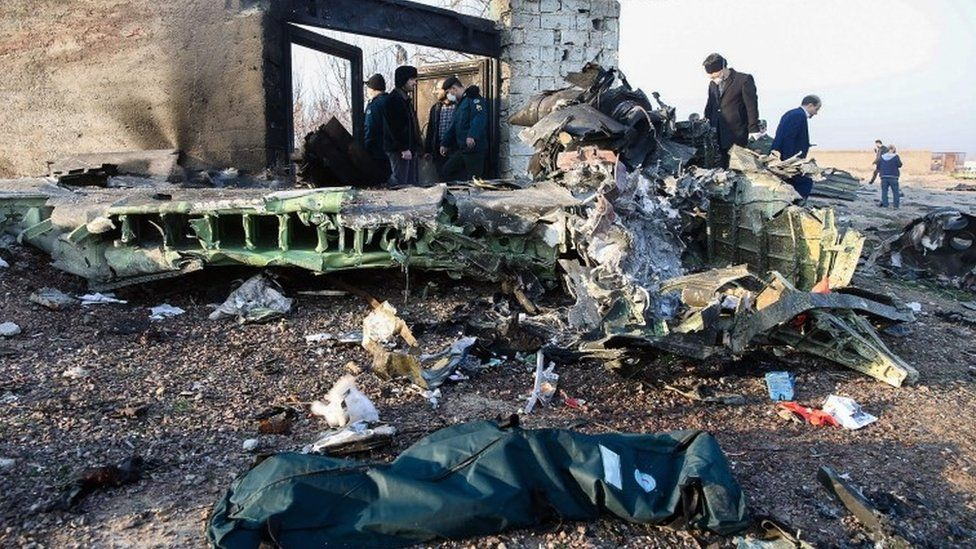 People stand near the wreckage after a Ukrainian plane carrying 176 passengers crashed near Imam Khomeini airport in Tehran on January 8, 2020