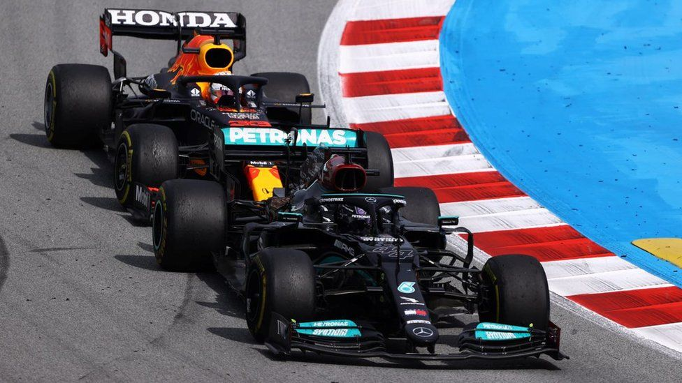 Max Verstappen and Lewis Hamilton battling on track