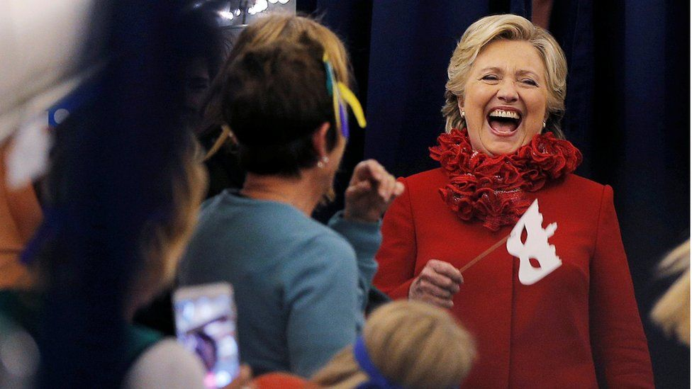 Hillary Clinton laughs as she holds a face mask
