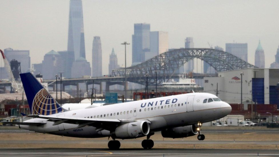 A United Airlines passenger jet takes off with New York City as a backdrop