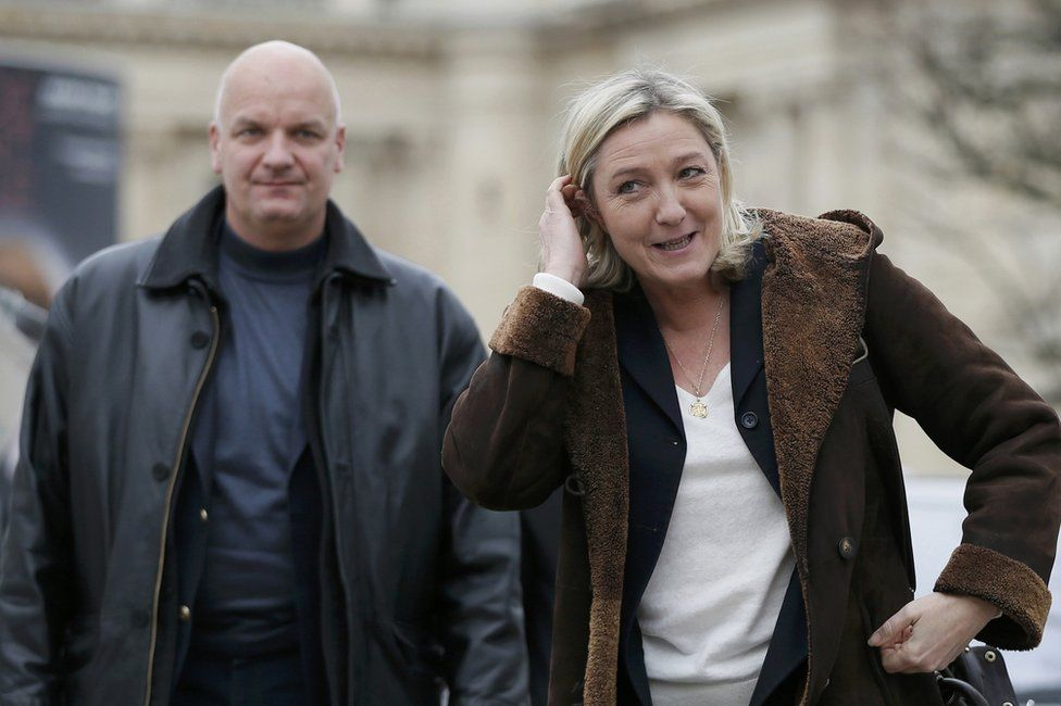 Marine Le Pen arrives with her bodyguard Thierry Legier (L) to visit the Christmas market on the Champs Elysees in Paris, France, 22 December 2014