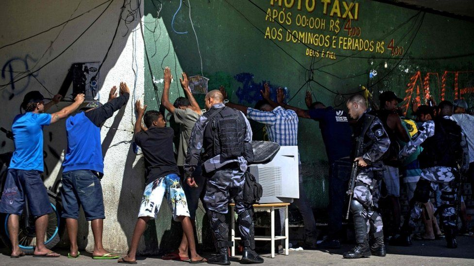PM militarized police officers frisk suspects in the Mangueira shanty town during a search and capture operation in Rio de Janeiro, Brazil on July 17, 2017