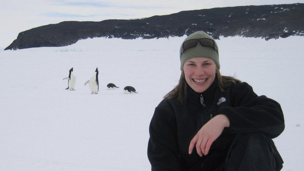 A woman kneels in the snow in front of some penguins