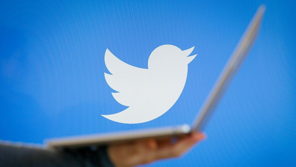 A Twitter logo (the white bird on a blue background) is seen in this photograph while a soft-focus foreground element shows a person's arm holding an open laptop
