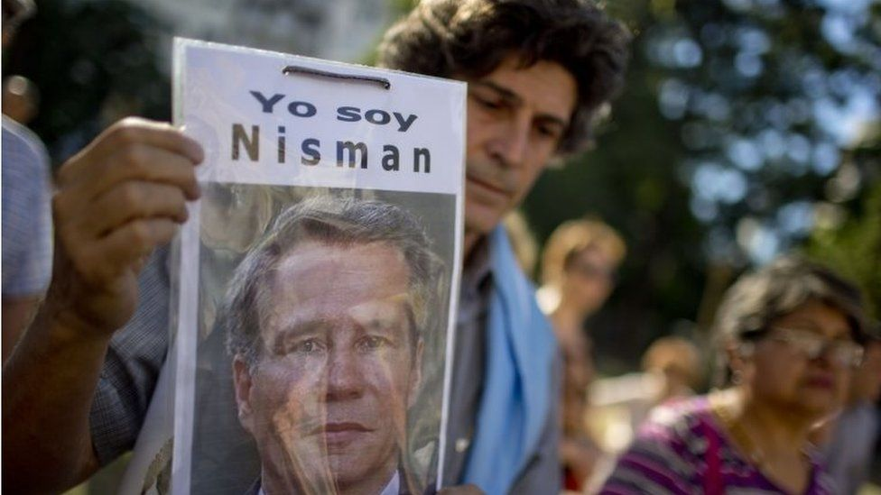 """In this 18 March, 2015 file photo, a demonstrator holds a photo of late prosecutor Alberto Nisman that reads in Spanish """"I am Nisman"""" at an protest outside a court house demanding justice, two months after his death in Buenos Aires, Argentina"""