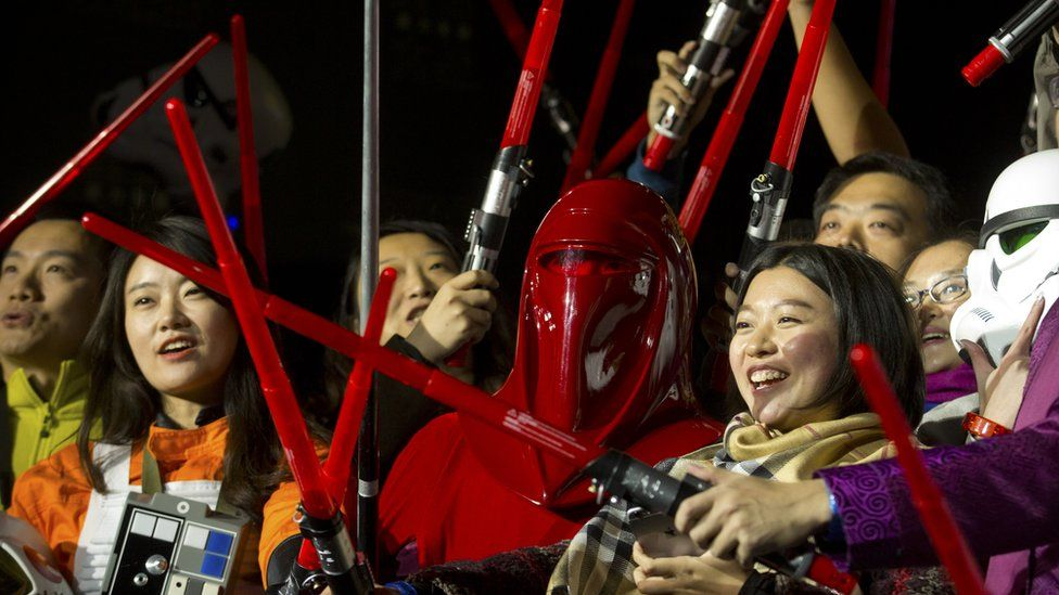 Chinese Star Wars fans hold light sabers during an event at the Great Wall of China