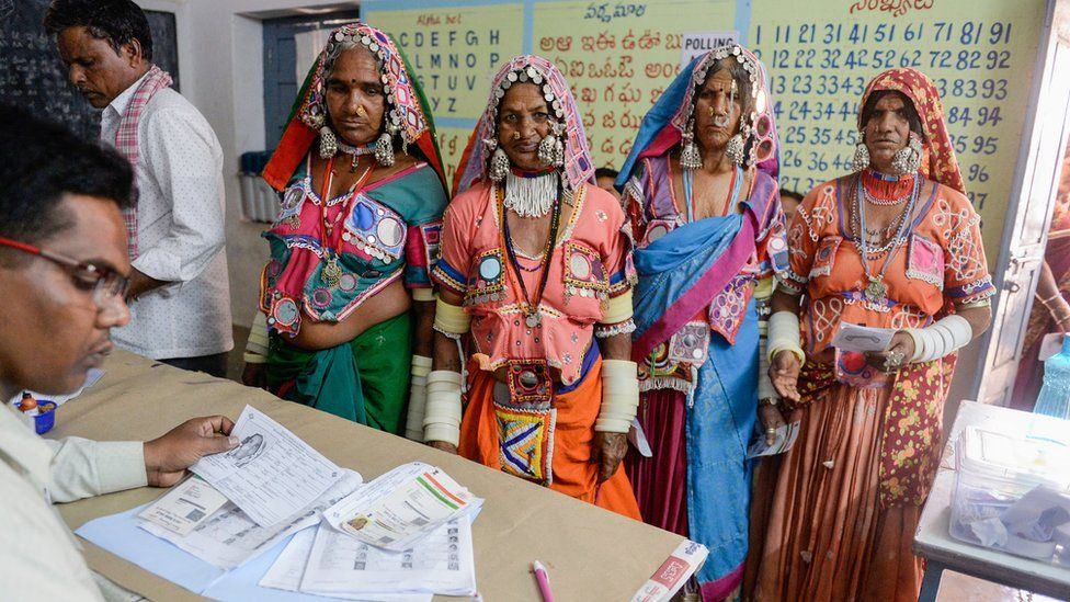 An official checks the names of Indian lambadi tribeswomen at a polling station during India's general election at Pedda Shapur village on the outskirts of Hyderabad on April 11, 2019.