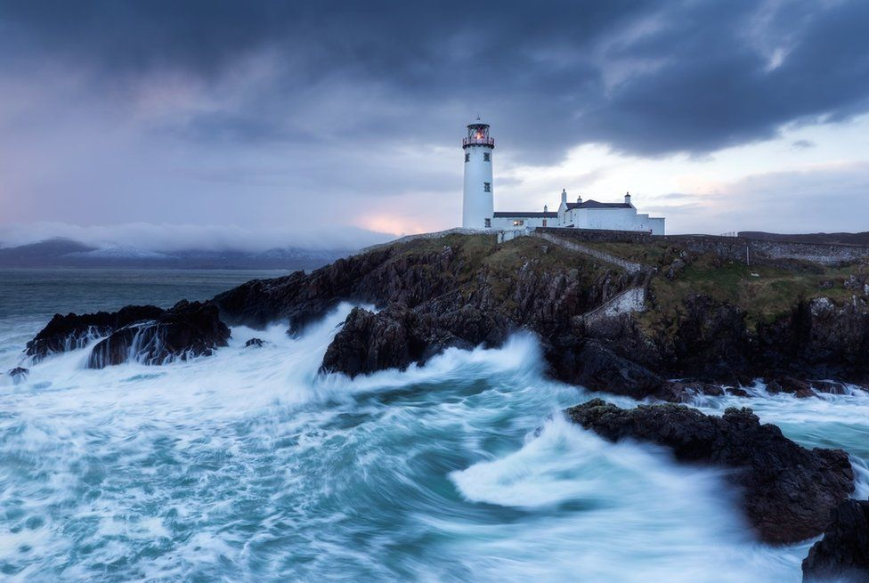 Storm clouds over Fanad lighthouse in County Donegal as waves crash against the rocks