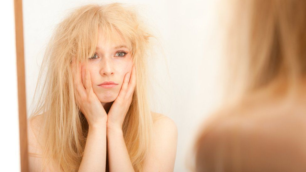 A young blonde woman, head in hands, fed up with her hair as she looks into the mirror