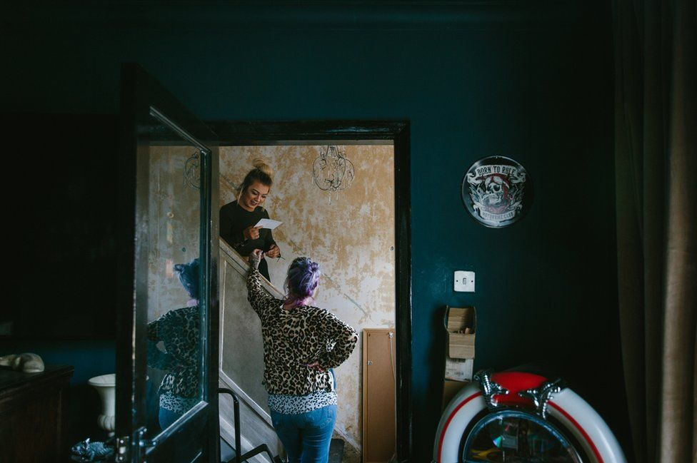 Melanie Semple chats with her daughter in the hallway of her home in Newcastle