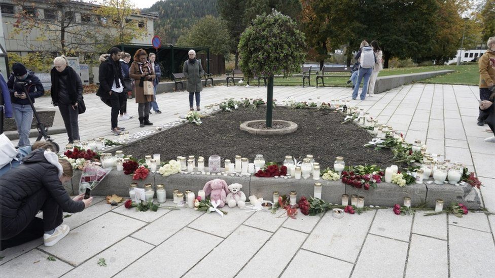 People in Kongsberg place tributes for the dead after an attack which left five people dead in the town