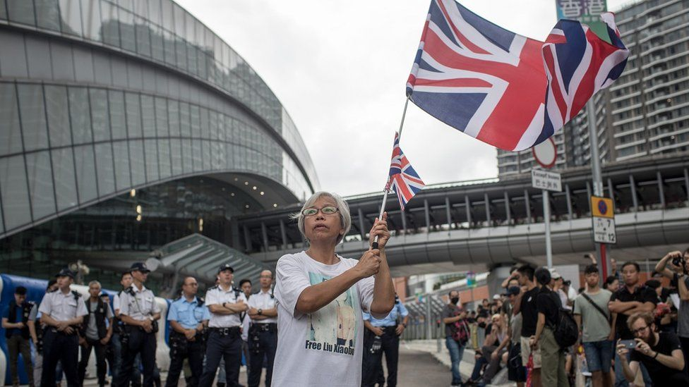 A protester waves a British flag in front of the West Kowloon railway station during a protest against the proposed extradition bill on July 7, 2019
