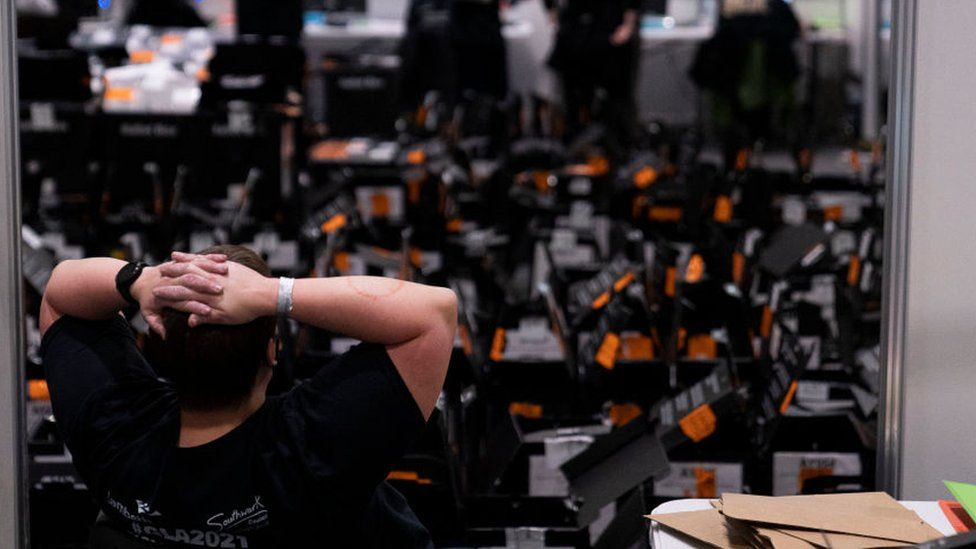 A volunteer relaxes after processing ballot papers at the ExCel Centre on May 07, 2021 in London, England.