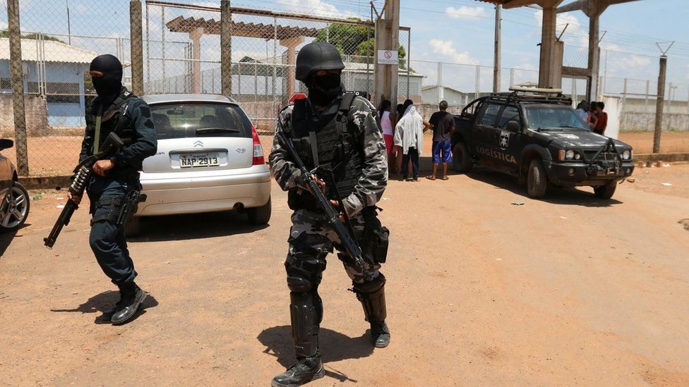 Riot police officers patrol outside a prison after clashes between rival criminal factions in Boa Vista, Brazil