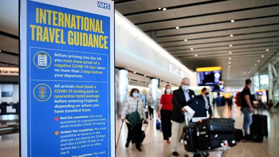 Travellers pass a sign at Heathrow