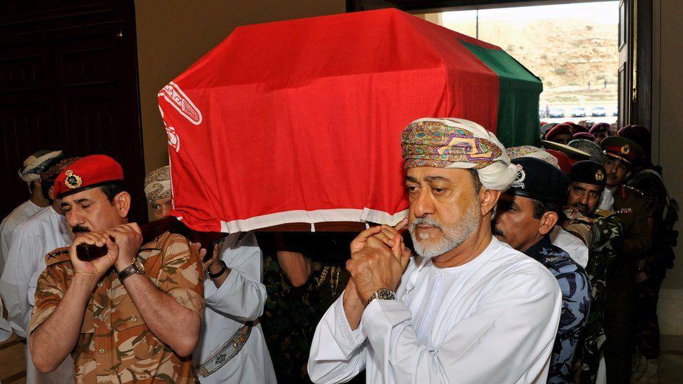 Oman's newly sworn-in Sultan Haitham bin Tariq al-Said carries the coffin of his cousin, the late Sultan Qaboos