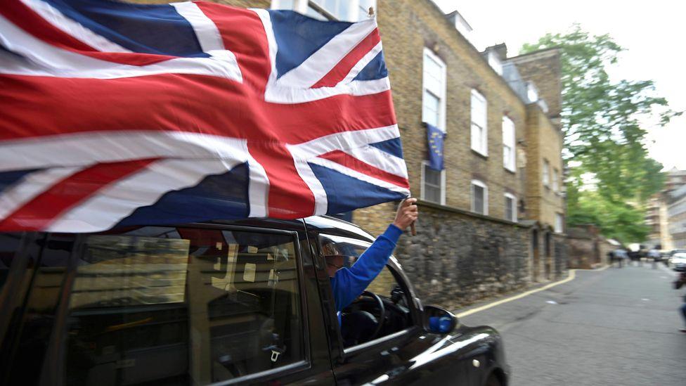 Black taxi driver waves Union Jack