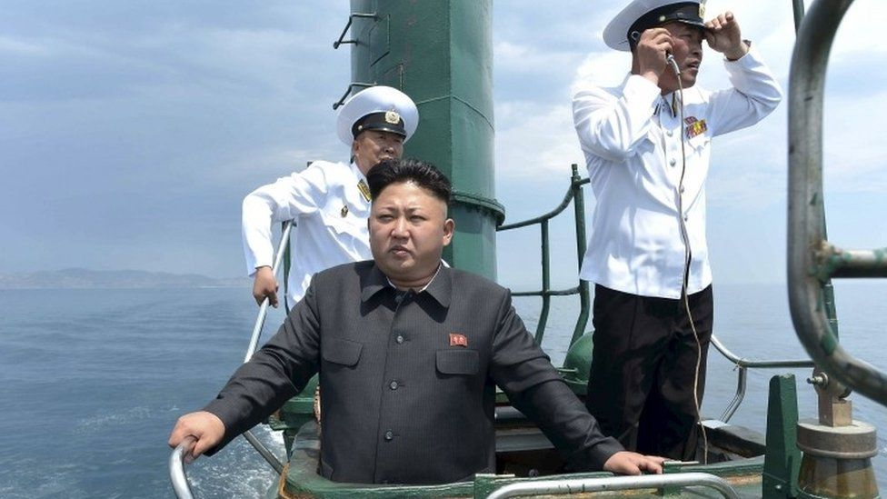 North Korean leader Kim Jong Un (front) stands on the conning tower of a submarine during an inspection in January 2016