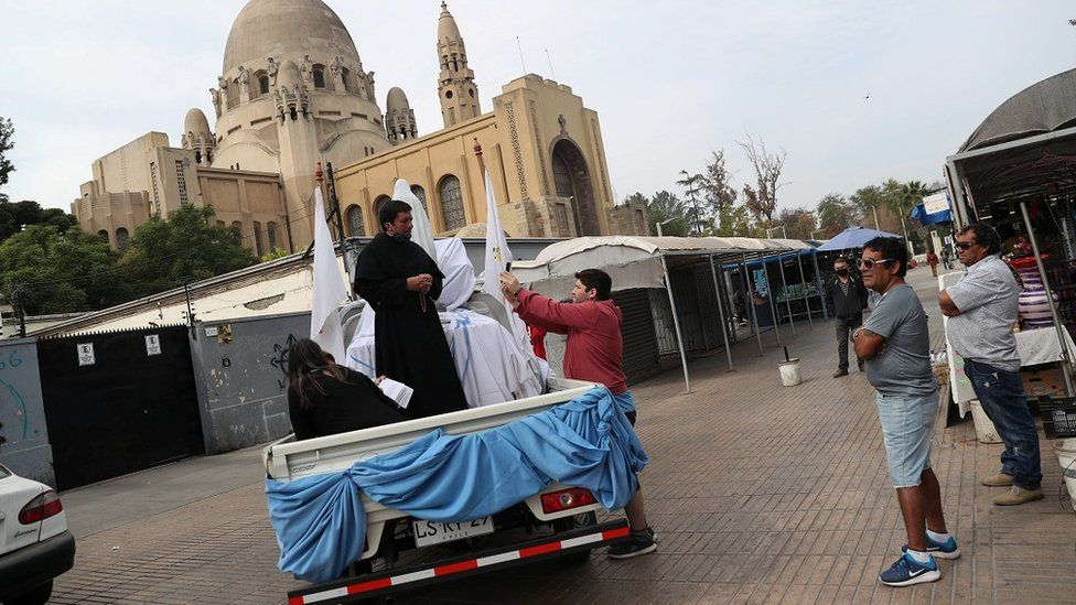 A priest uses a van to give blessings during Easter Saturday in Santiago, Chile