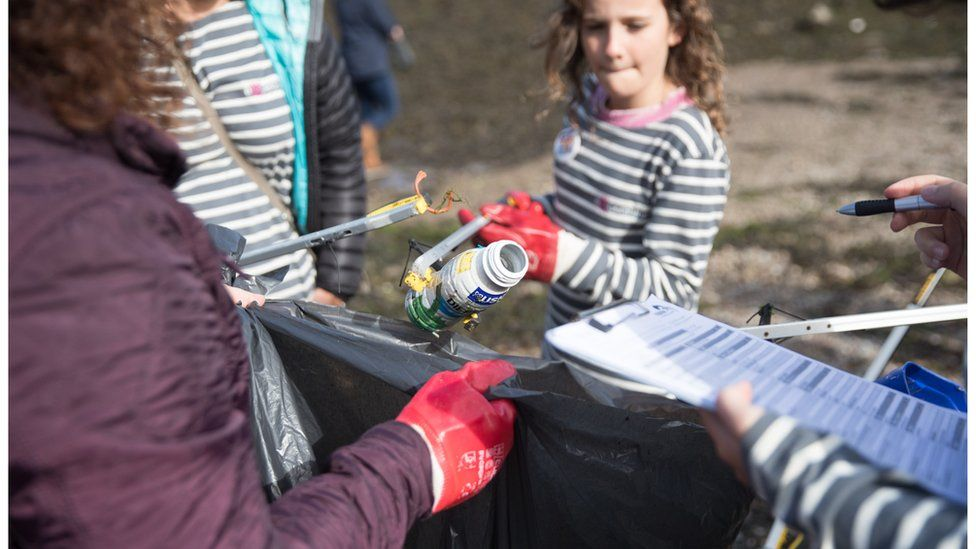 Volunteers litter pick waste from the coastline
