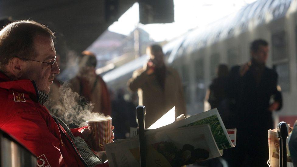 Commuter drinking coffee on railway platform in Hamburg