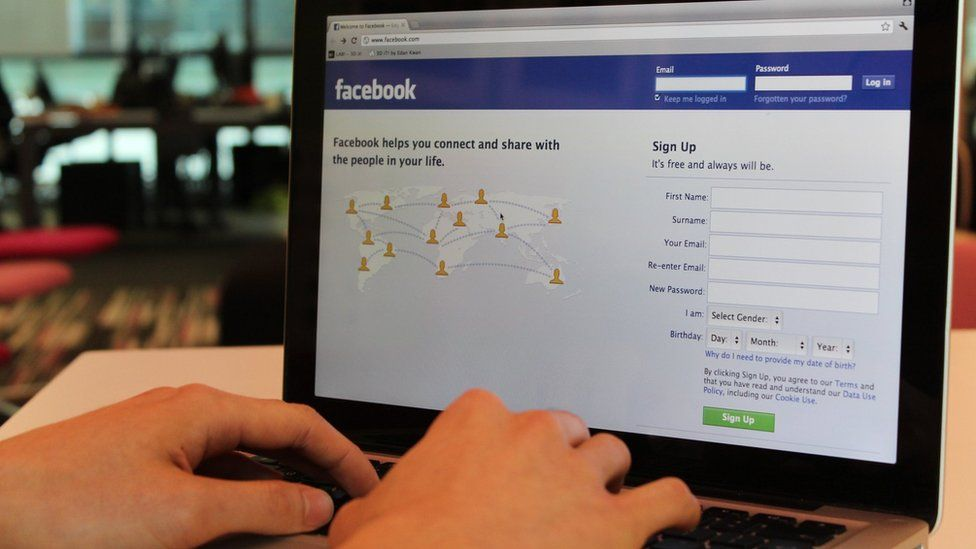 A person using a laptop. Facebook is displaying on the screen