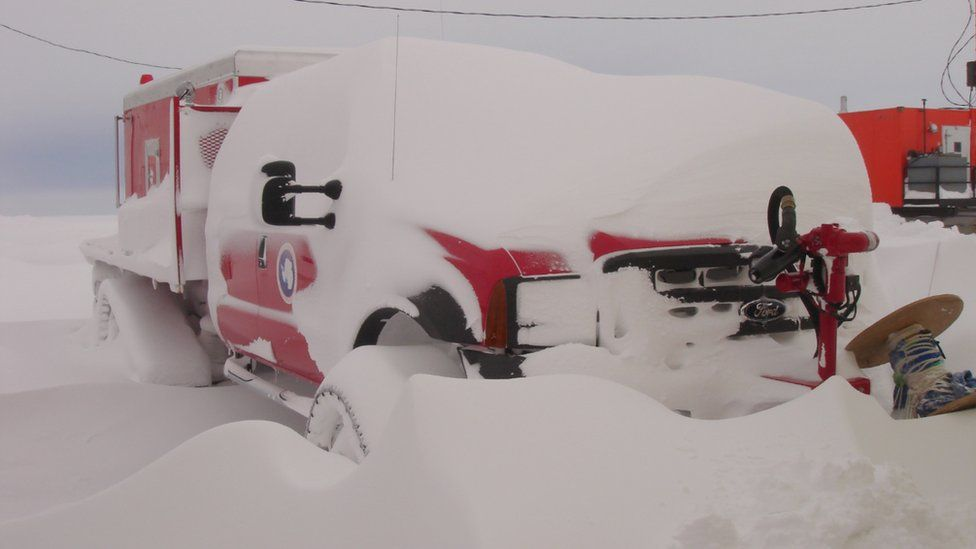 An emergency vehicle partially covered in snow