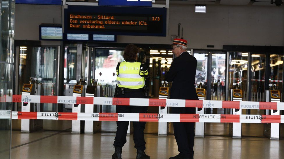 Officials stand inside a cordoned-off area at The Central Railway Station in Amsterdam on August 31, 2018,