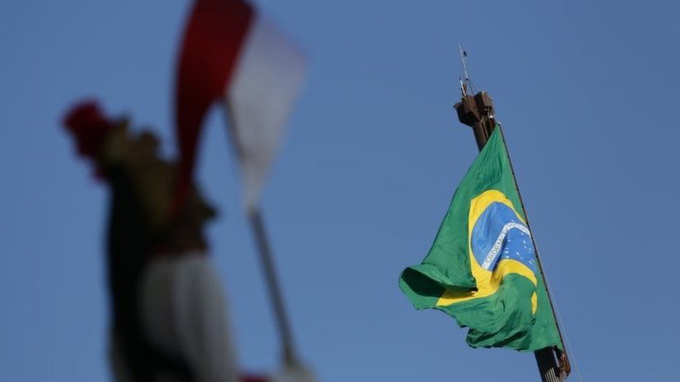 A soldier of the presidential guard stands at attention as the flag of Brazil flies in the background, in front of the Planalto Presidential Palace, in Brasilia (12 April 2016)