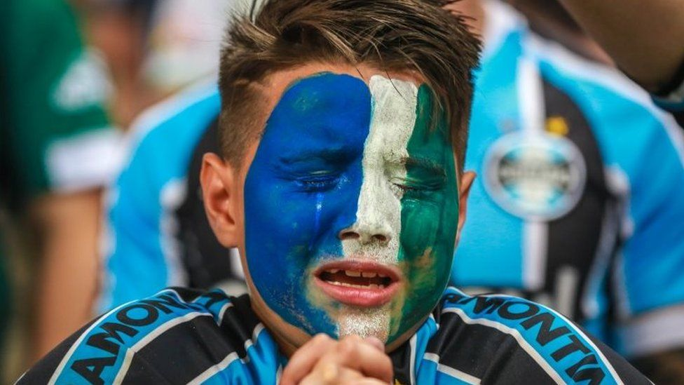 Fans of Gremio react during an homage for the Brazilian team Chapecoense Real victims of a plane crash in Colombia on November 29, ahead of the match between Atletico Mineiro and Gremio for the Copa do Brasil 2016 final at Mineirao stadium in Porto Alegre, Brazil, on December 7, 2016