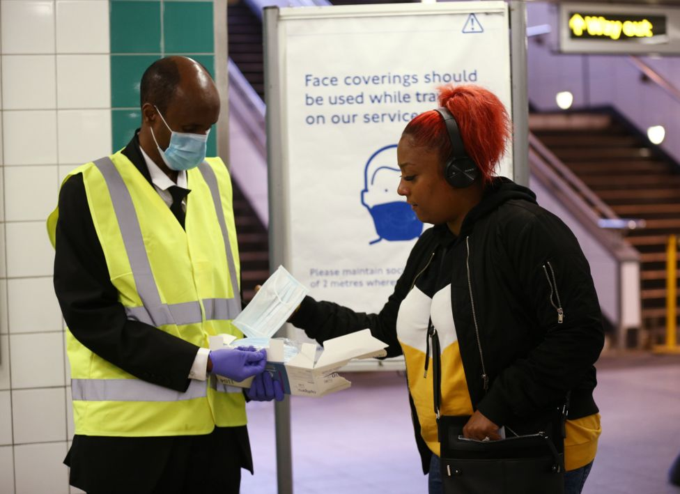 London Underground worker handing out face coverings to commuters
