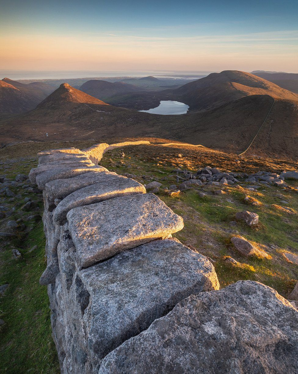 Sunset over the Mourne wall leading to Slieve Doan and Carn mountain as seen from Slieve Loughshannagh in the Mourne mountains in County Down