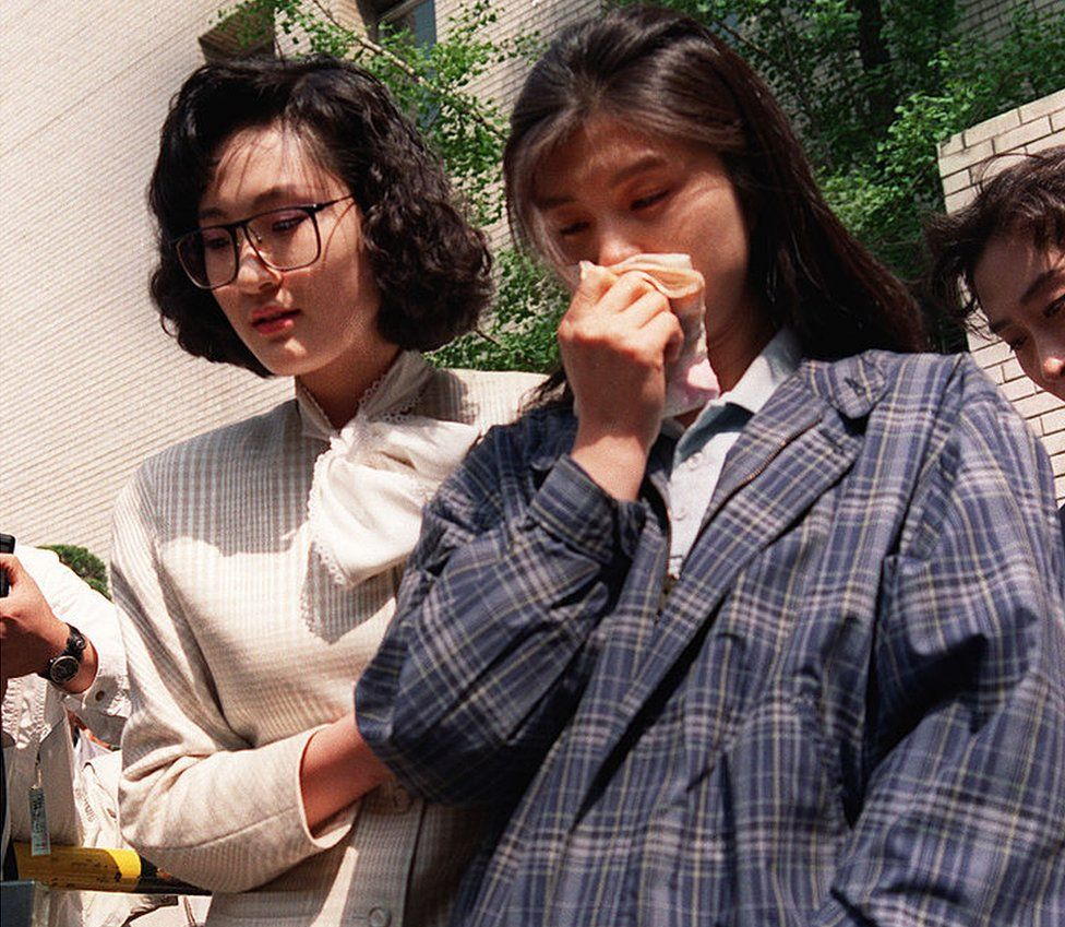 Kim Hyun-hui holds a handkerchief to her nose as she is led from a courtroom in Seoul by a woman investigator, on 25 April 1989