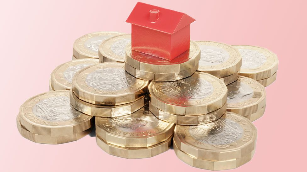 Miniature red house resting on a pile of pound coins.