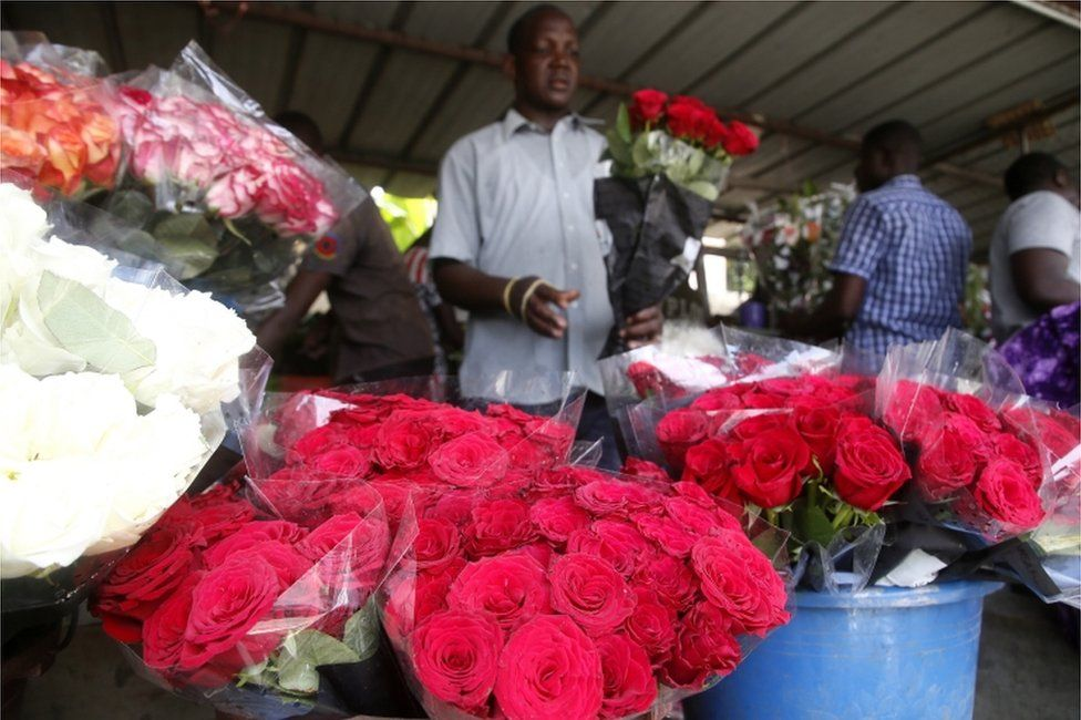 A man sells roses of various colours from an outdoor stall in Abidjan, Ivory Coast - Friday 12 February 2021