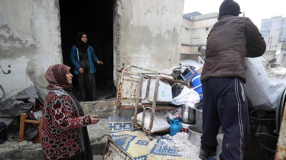 A displaced Syrian woman watches as her belongings are unloaded at a makeshift camp in opposition-held Idlib province, Syria (31 December 2019)