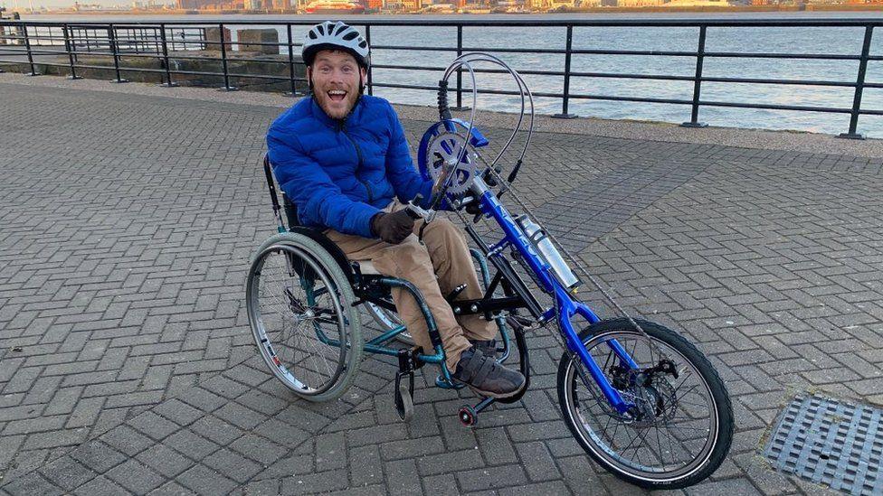 Journalist Ellis Palmer using his handcycle
