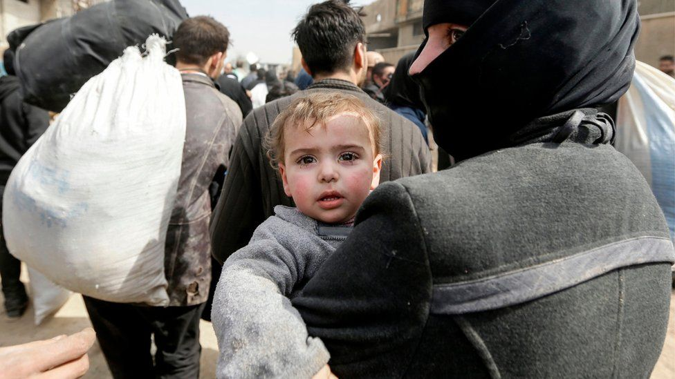 A Syrian woman carrying a child evacuated from the Eastern Ghouta