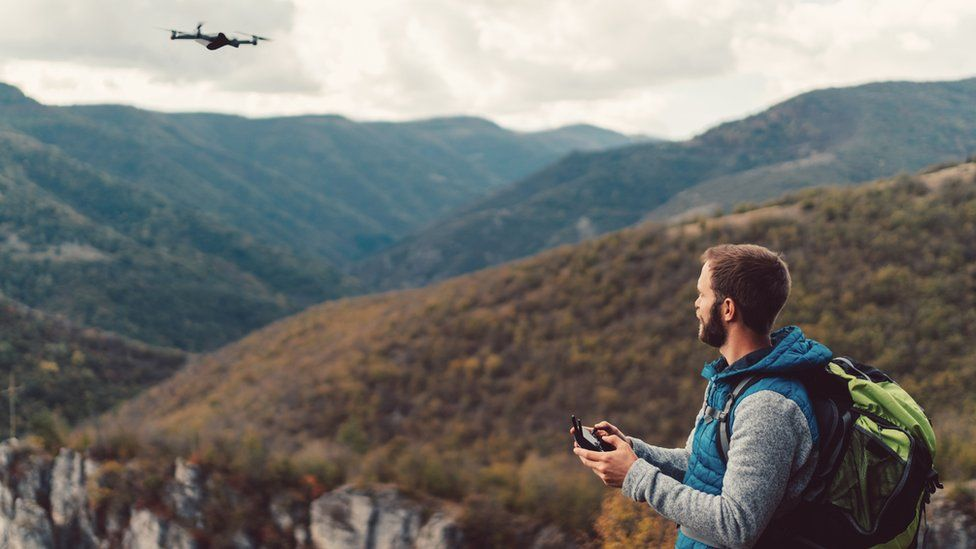 A man flying a drone on a mountain top