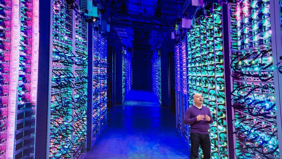 A man standing in a data centre with rows and rows of stacked server machines stretching into the distance