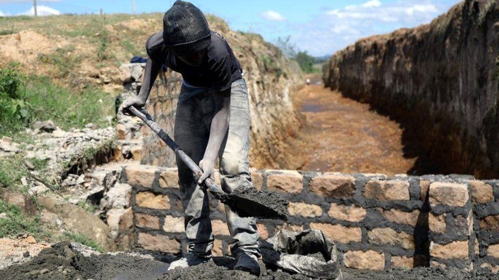 A man mixes mortar as he repairs a bridge broken by flooding waters near the Rift Valley town of Mai Mahiu, Kenya November 27, 2019