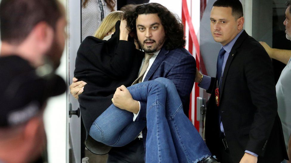 Lawyer Danilo Garcia de Andrade is pictured carrying Ms Trindade