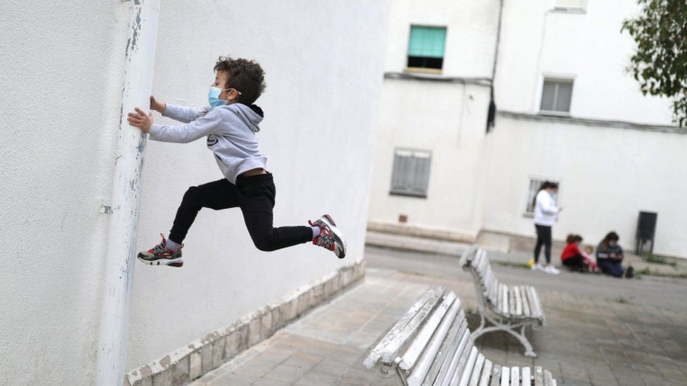 Kilian, 6, wears a protective face mask as he jumps from a bench, after restrictions were partially lifted for children, during the coronavirus disease (COVID-19) outbreak, in Igualada, Spain, on 26 April 2020