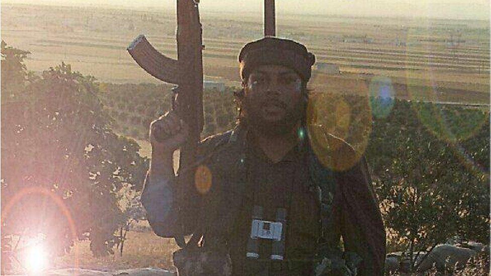 Abu Aziz holding a gun