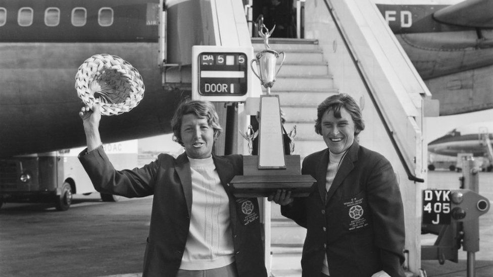 Cricketers Rachael Heyhoe Flint (left) and Lynne Thomas at London Airport (now Heathrow) on their return from the West Indies, 4 March 1971. They are holding the Pearl And Dean Cricket Trophy for competition between the English and West Indies Ladies' teams.