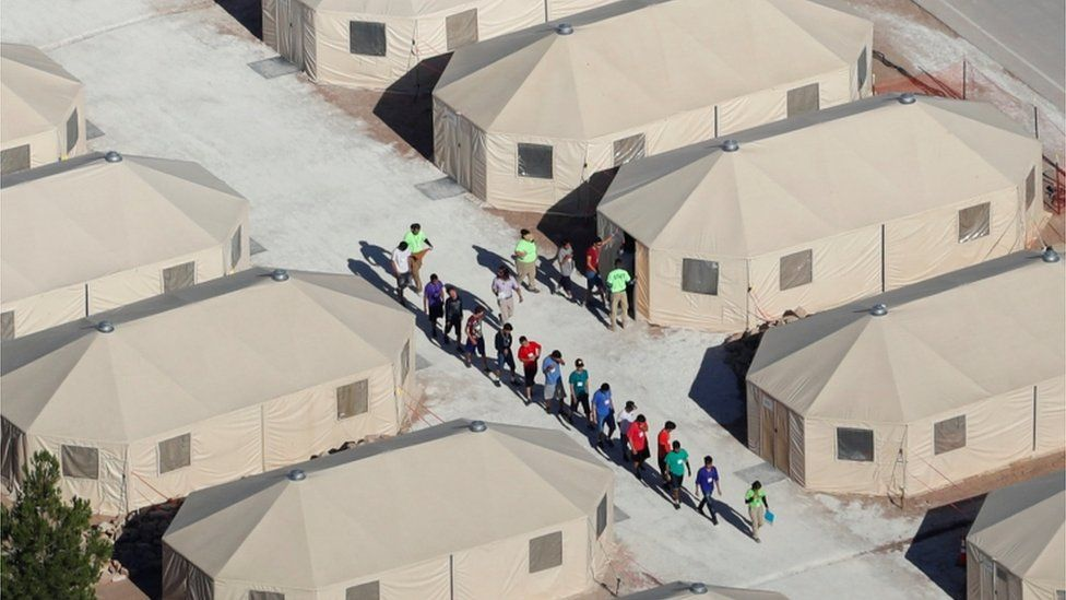 Children walking between tents at the Tornillo camp in Texas