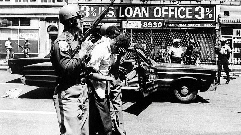Police officers arrest black suspects on a Detroit street on 25 July 1967.